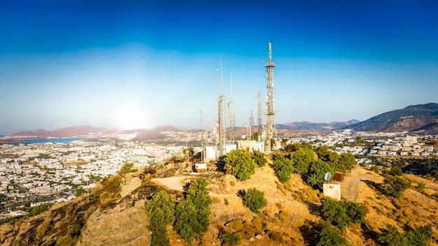 Tour de télécommunication sur le mont avec antenne de réseau cellulaire 4g 5g sur fond de ville