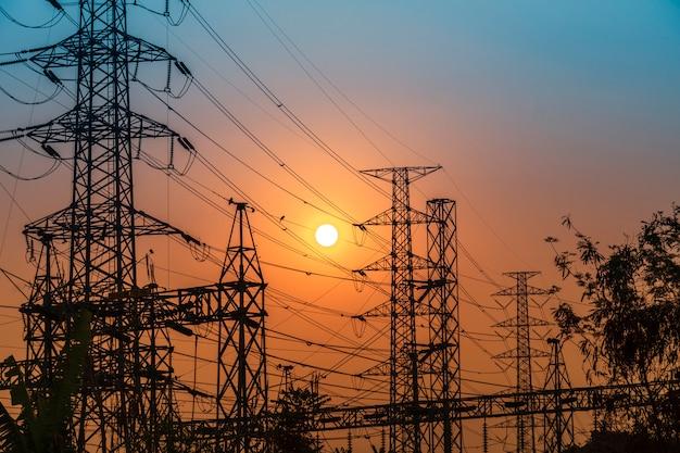 Tour de transmission en acier haute tension au coucher du soleil