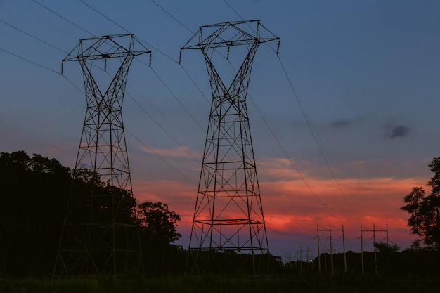 Tour de transmission de puissance se découpant contre la lueur du coucher du soleil