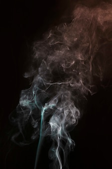 Tourbillon de fumée blanche et turquoise sur fond noir foncé