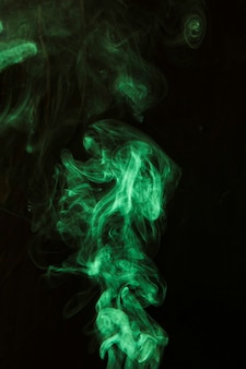 Tourbillon de fumée verte sur fond noir foncé