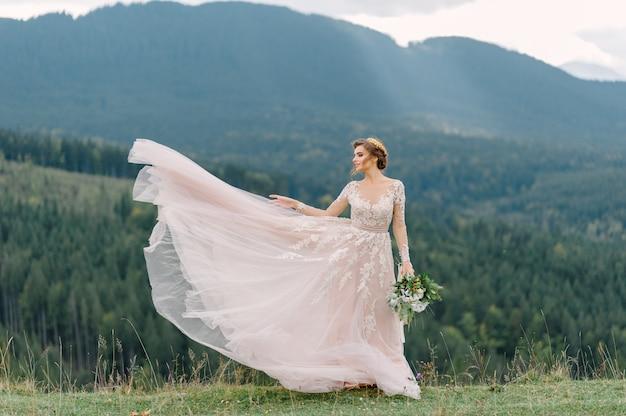 Tourbillonnant mariée tenant la jupe de voile de robe de mariée à la forêt de pins