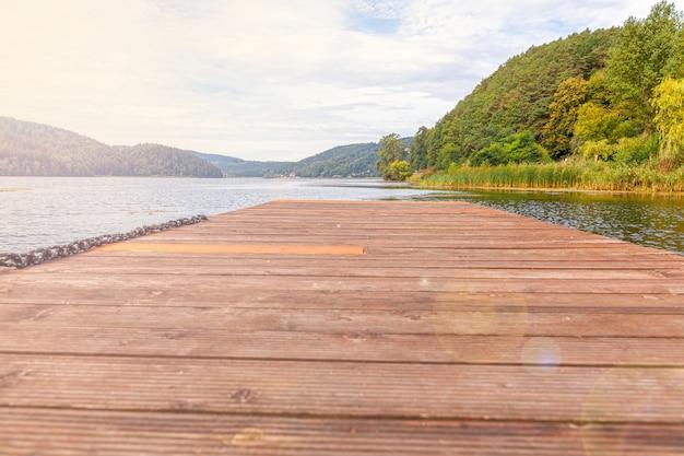 Tourisme de pêche relax concept. beau lac de forêt ou rivière par une journée d'été ensoleillée et vieux quai ou jetée en bois rustique