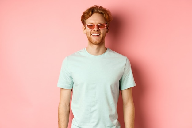 Tourisme et vacances concept gai homme barbu roux en lunettes de soleil et tshirt souriant et looki ...