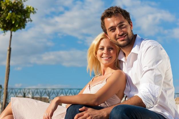 Tourisme en ville - couple en vacances sur un banc