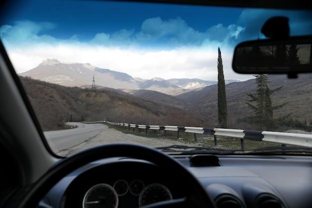 Tourisme. voyage en voiture. vue sur route et montagne à travers le pare-brise. mise au point sélective.