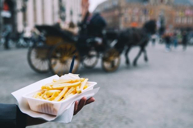 Tourist détient la malbouffe de rue populaire frites en hollande amsterdam pays-bas
