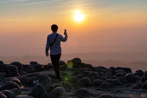 Tourist holding mobile phone sur le sommet de la montagne en pierre nodulaire en soirée, point de vue de lan hin poom, thaïlande