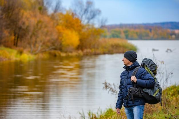 Tourist tient un sac à dos avec sa main et regarde la beauté de la nature autour de lui à l'automne près de la rivière
