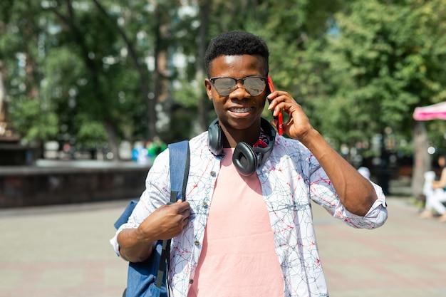 Touriste africain en lunettes de soleil avec téléphone portable