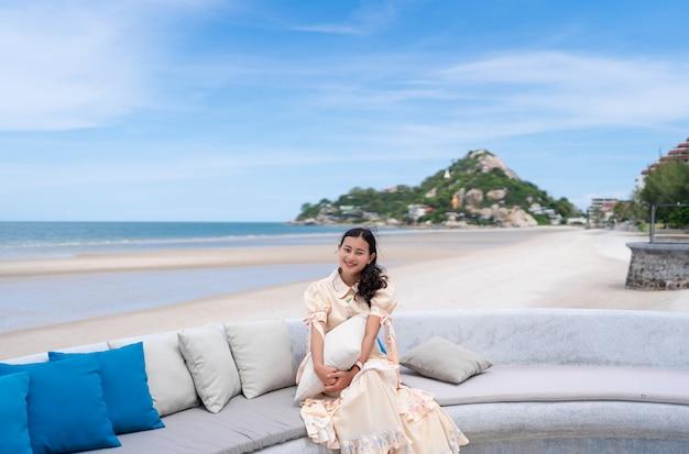 Une touriste asiatique heureuse s'assoit et tient un oreiller sur un canapé avec vue sur la mer bleue et la montagne à huahin, thaïlande, une fille se détend en vacances en été