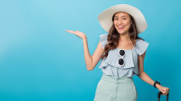 Touriste asiatique jolie femme se préparant à voyager en pointant la main pour copier l'espace de côté et tenant les bagages.