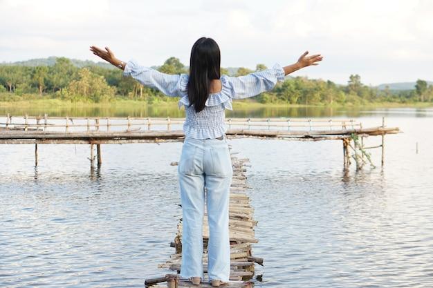 Une touriste asiatique marche sur un pont de bambou
