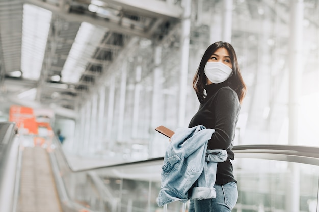Touriste asiatique portant un masque facial tenant un passeport