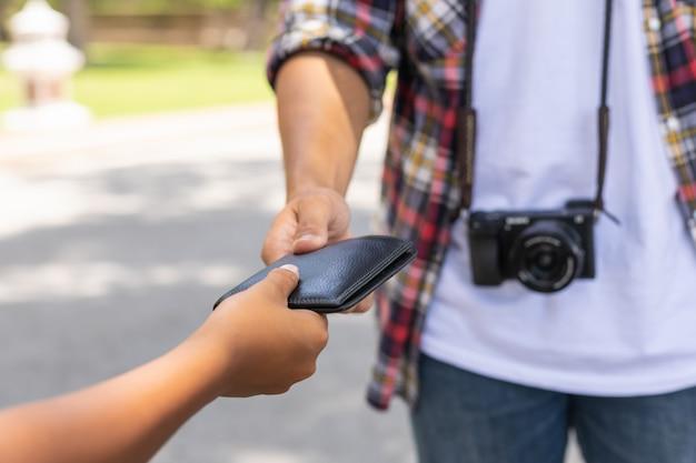 Touriste asiatique ramassant son portefeuille noir parmi d'autres personnes qu'ils ont trouvées dans une attraction touristique