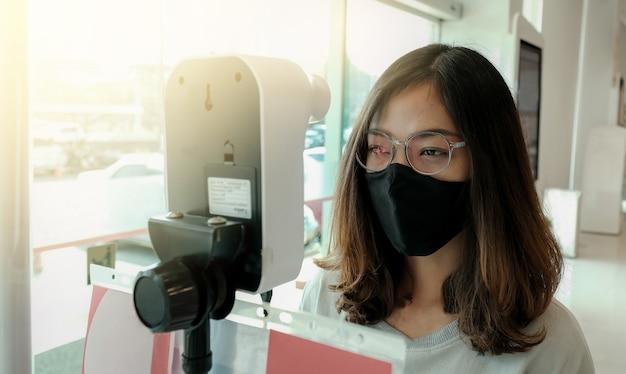 La touriste asiatique a vérifié la température corporelle avec un scanner thermique