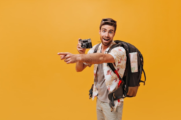 Touriste barbu avec de beaux yeux en tenue d'été cool regardant dans la caméra et posant avec un grand sac à dos sur un mur isolé
