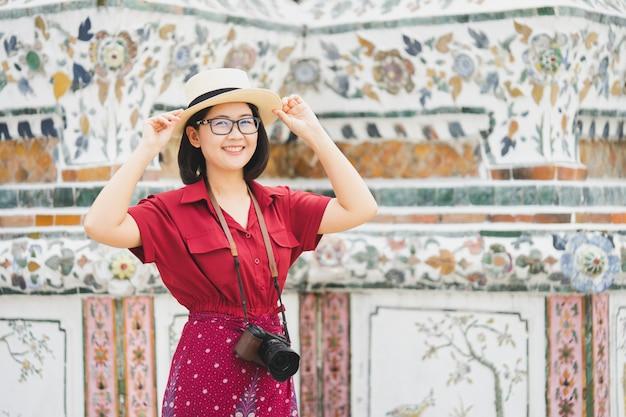 Touriste belle femme tenue de caméra pour capturer les souvenirs. temple wat arun en thaïlande.