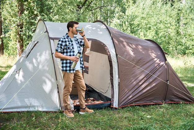 Touriste boit du thé près de la tente de camping dans une forêt
