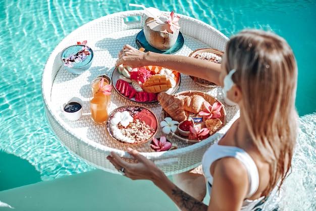 Une touriste caucasienne en bikini mange de la nourriture exotique et nage dans une piscine à l'hôtel pendant ses vacances en thaïlande.