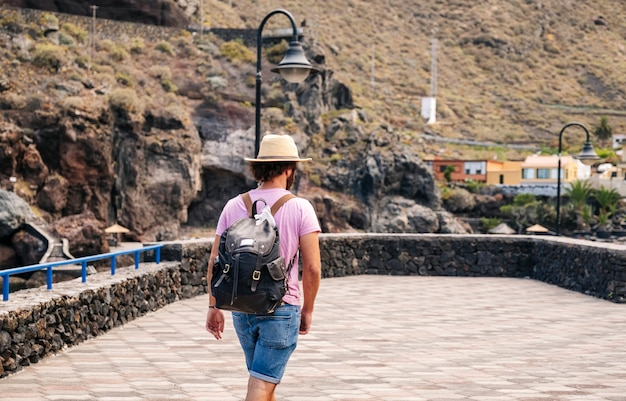 Un touriste avec un chapeau et un sac à dos par une ville côtière el hierro, îles canaries
