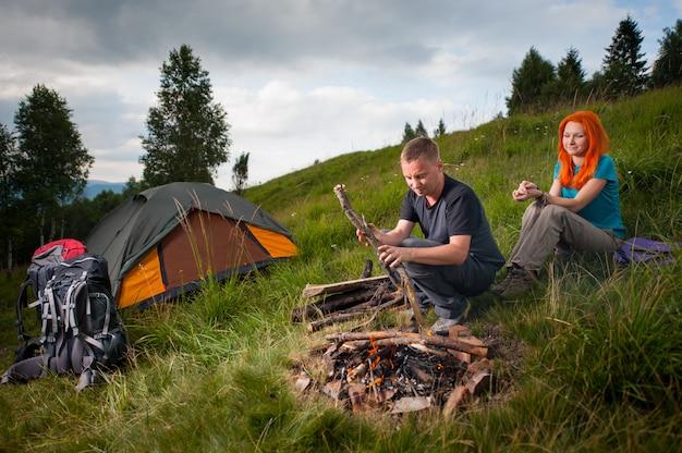 Touriste sur la colline jette du bois dans le feu de camp, ensuite sur l'herbe verte