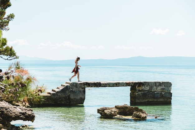 Touriste dans un bel endroit voyageant après le verrouillage se sentant libre en profitant de la vue sur la mer et l'air frais