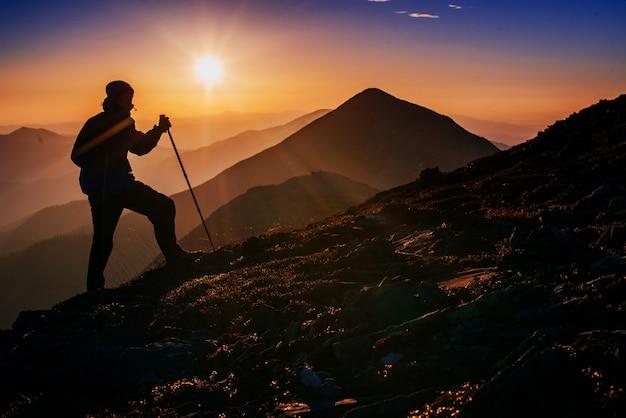 Touriste dans les montagnes au coucher du soleil