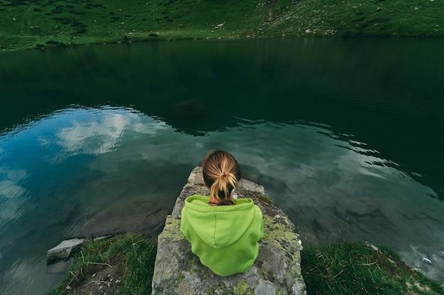 Une touriste est assise sur une pierre près du lac au pied des montagnes. tourisme, repos, loisirs.
