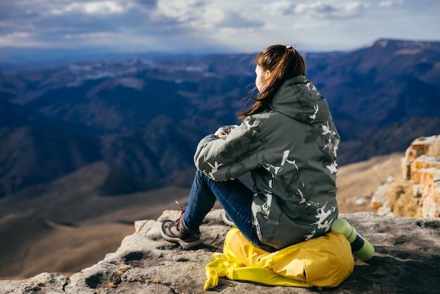 Une touriste est assise sur un sac à dos à l'arrière-plan des hautes montagnes