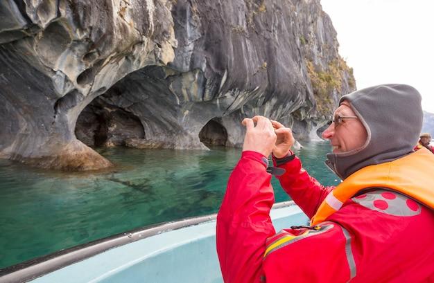 Touriste en excursion en bateau vers des grottes de marbre inhabituelles sur le lac de general carrera, patagonie, chili