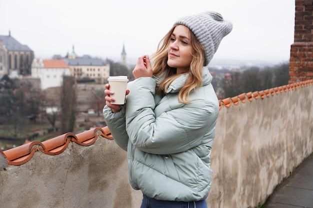 Touriste féminin dans le contexte de la ville en république tchèque - kutna hora. elle boit du vin chaud - saison d'automne