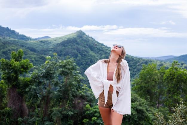 Touriste femme élégante européenne se dresse au sommet de la montagne avec une vue tropicale incroyable de l'île de koh samui thaïlande mode portrait en plein air de femme