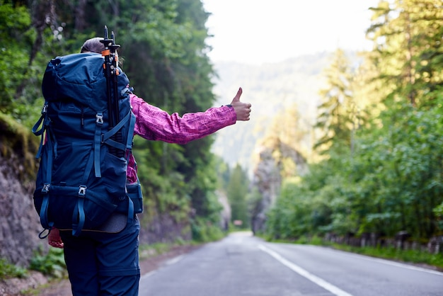 Touriste femme faisant de l'auto-stop sur une route de montagne vide