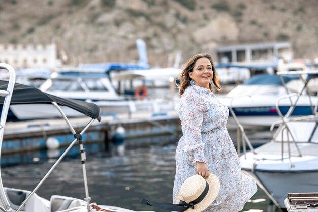 Touriste femme marche sur la jetée de lande en bois avec des yachts touristiques