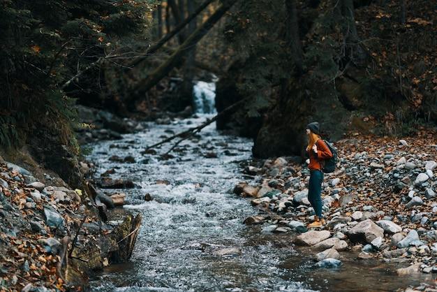Touriste de femme photographiant des montagnes de forêt de rivière de nature
