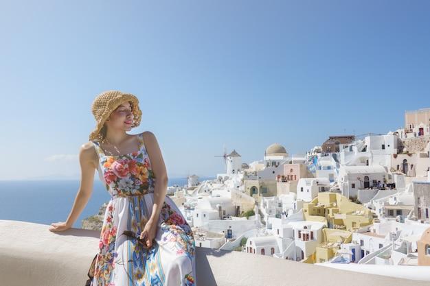 Touriste femme en robe de flore visitant village blanchi à la chaux à oia, santorin, grèce. mer méditerranée.