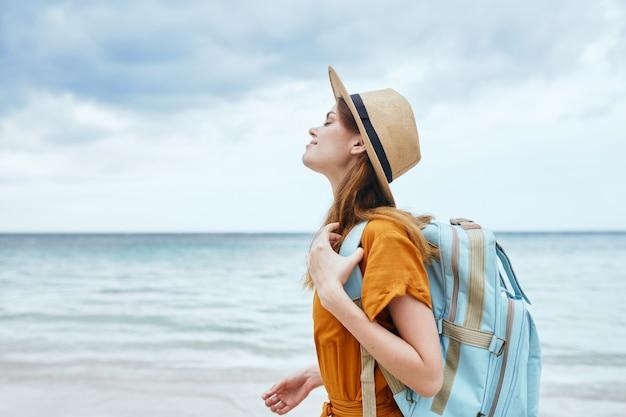 Touriste de femme avec le sac à dos sur l'air frais de voyage de plage
