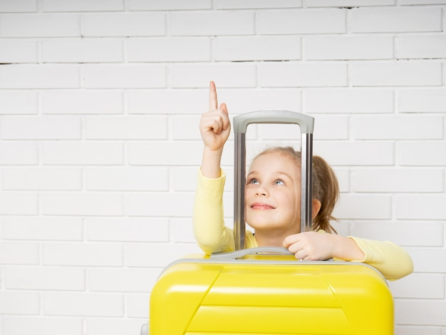 Touriste de fille heureuse avec une valise jaune pointant vers le haut sur un fond de briques blanches
