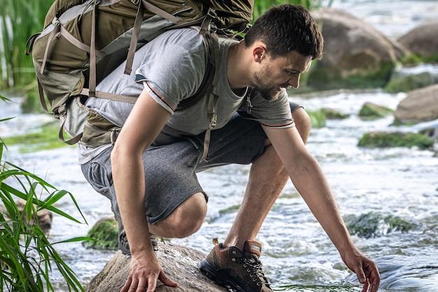Un touriste avec un grand sac à dos de randonnée se rafraîchit près d'une rivière de montagne dans la chaleur estivale.