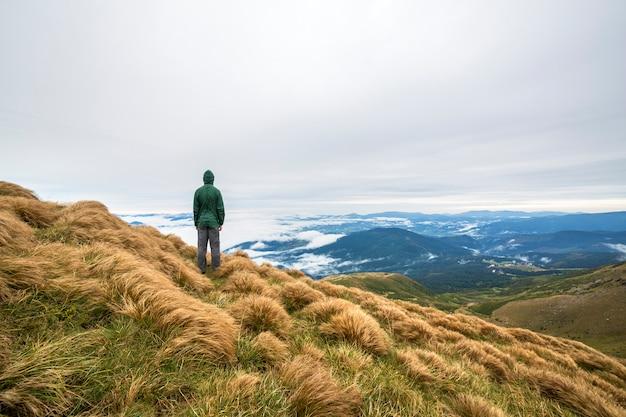 Touriste grimpeur mâle debout sur la pente de la colline herbeuse sur les montagnes vertes avec des nuages gonflés blancs et ciel bleu