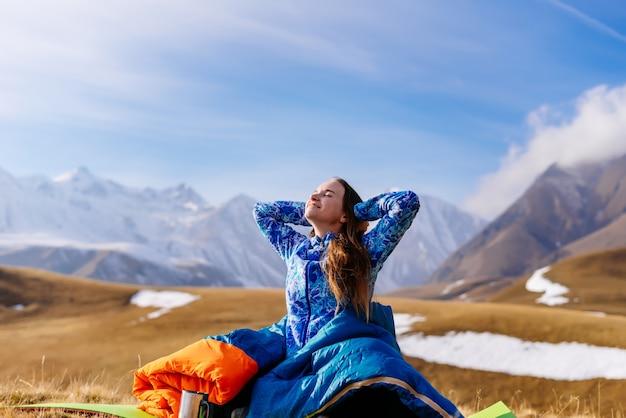 Une touriste heureuse s'assoit sur le fond des montagnes et s'arrête