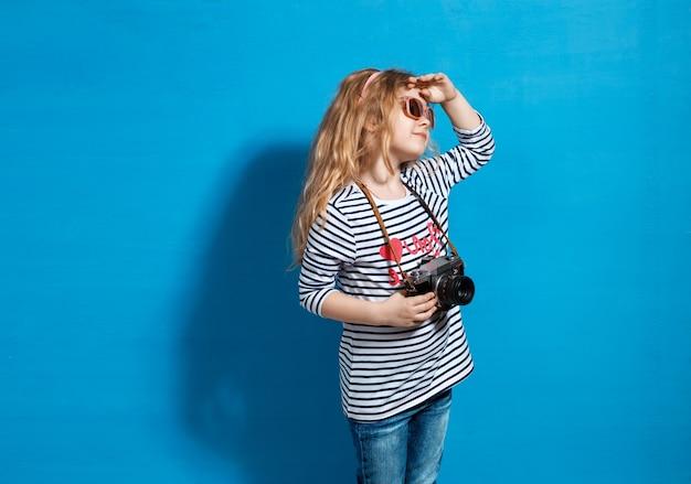 Touriste heureux de fille d'enfant avec la caméra rétro au mur bleu.