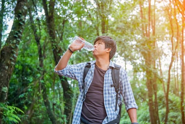Touriste de hipster heureux homme avec sac à dos de l'eau potable tout en randonnée dans la forêt de la nature.