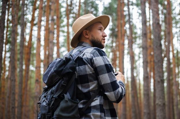Touriste homme avec des jumelles lors d'une randonnée dans la forêt. randonnée en montagne ou en forêt.