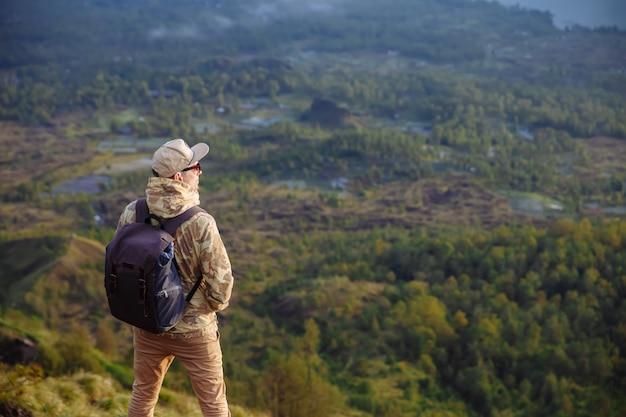 Touriste homme regarde le lever du soleil sur le volcan batur sur l'île de blai en indonésie. randonneur homme avec sac à dos voyage sur le volcan, concept de voyage