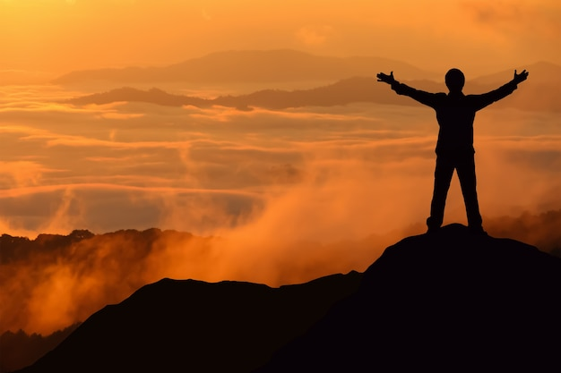 Touriste homme silhouette répandre la main sur la montagne supérieure.