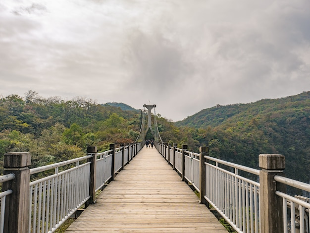 Un touriste inconnu qui marche sur un pont suspendu traverse la montagne au mont tianmen zhangjiajie en chine