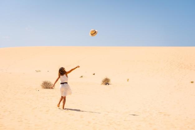 Touriste jetant son chapeau très heureux dans les dunes du parc naturel de corralejo, fuerteventura, îles canaries. espagne