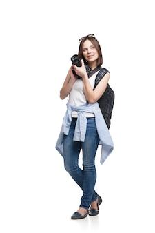 Touriste de jeune femme avec la caméra et le sac à dos, d'isolement sur le blanc